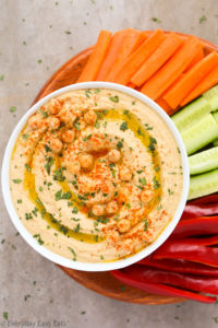 Overhead view of a bowl of Easy & Healthy Homemade Hummus Without Tahini with chopped vegetables on a neutral background.