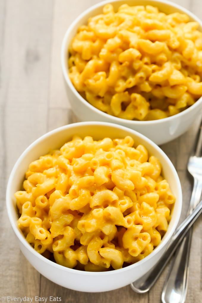 Budget-Friendly Meal: Overhead view of two bowls of Macaroni and Cheese with forks on the side on a wooden background.
