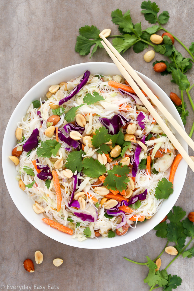 Overhead view of a bowl of Thai Noodle Salad with Coconut-Lime Dressing with chopsticks on a grey background.