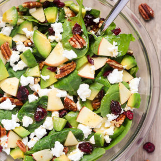 Overhead view of Apple Avocado Spinach Salad in a glass serving bowl on a wooden background.