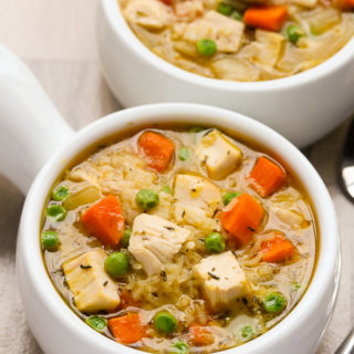 Close-up overhead view of two bowls of One-Pot Chicken and Rice Soup on a beige background.