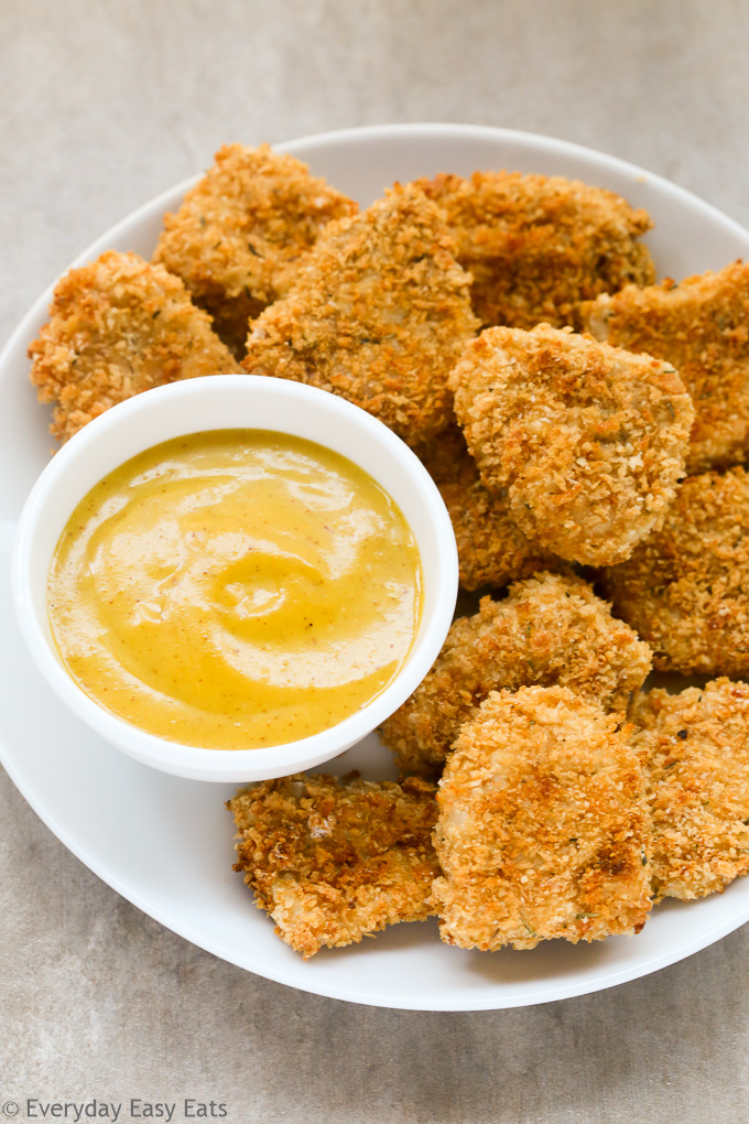 Overhead view of Baked Chicken Nuggets in white plate with a small dipping bowl of Honey Mustard Sauce on the side.