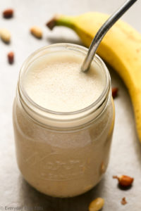 Overhead view of Peanut Butter Banana Protein Shake Recipe in a mason jar with a metal drinking straw against a beige background.
