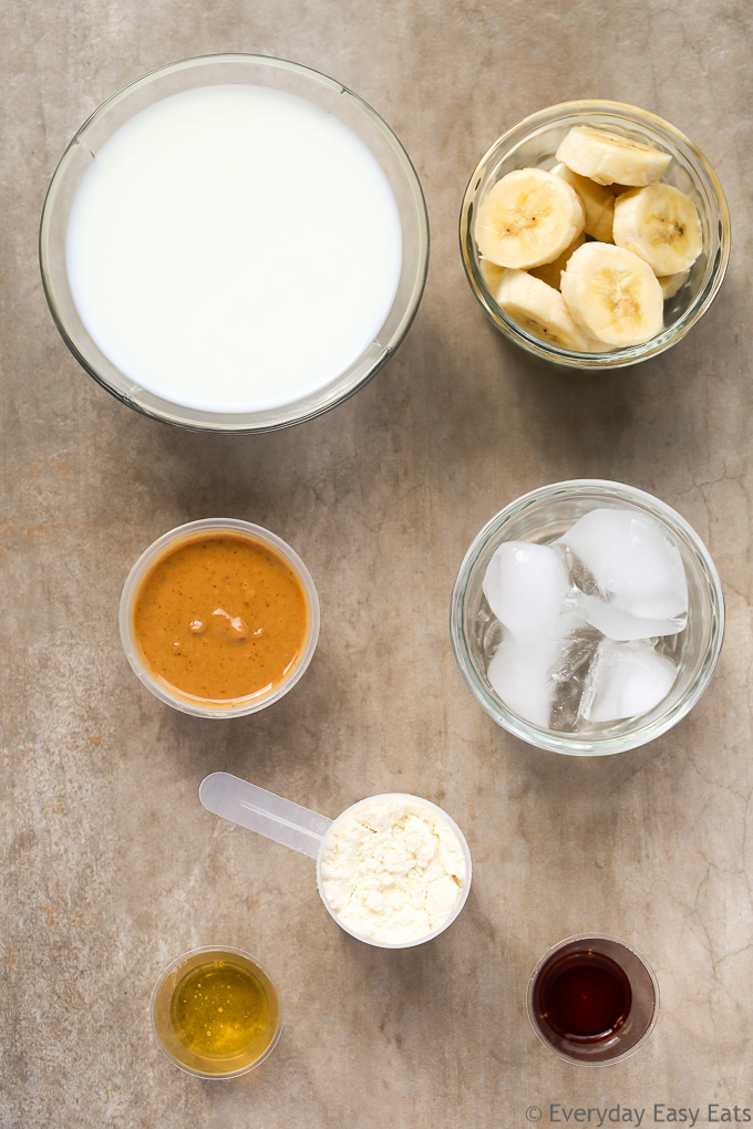 Overhead view of Peanut Butter Banana Protein Shake Recipe ingredients on a beige background.
