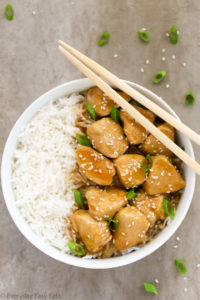 Overhead view of a bowl of Healthy Honey Teriyaki Chicken with rice and chopsticks on a grey background.