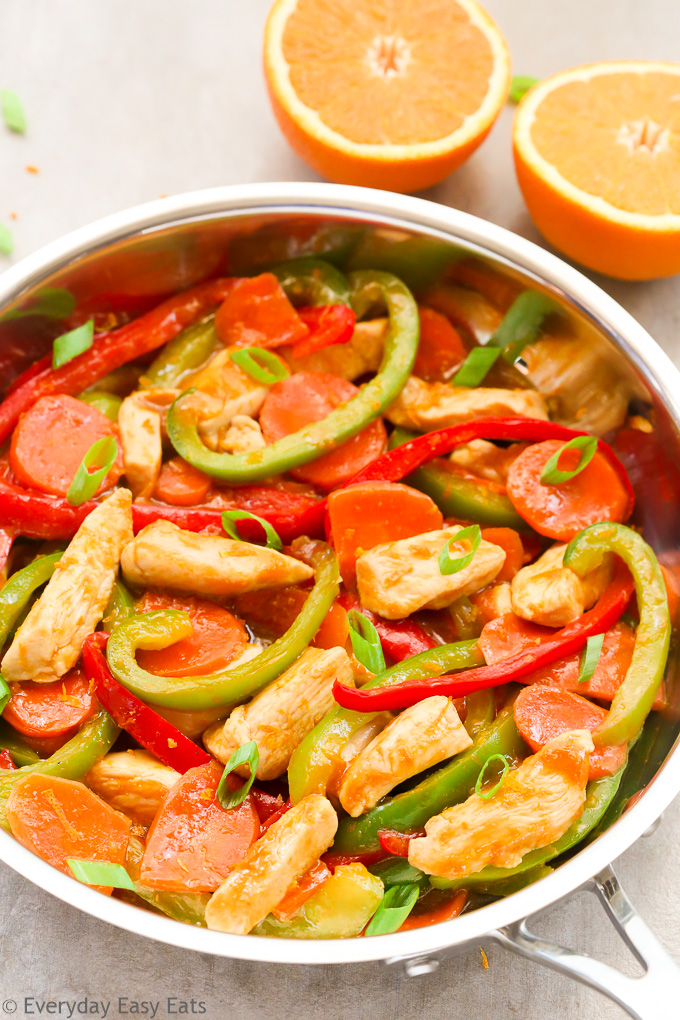 Side overhead view of Healthy Orange Chicken Stir-Fry in a wok on a light background.