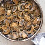Close-up overhead view of Sautéed Mushrooms and Onions in a skillet with a kitchen towel wrapped around the handle.