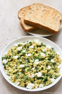 Overhead view of a plate of Scrambled Eggs with Spinach with toast on the side on a neutral-colored surface.