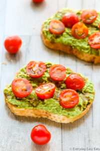 Side overhead view of two slices of Tomato Avocado Toast with scattered cherry tomatoes on a wooden background.