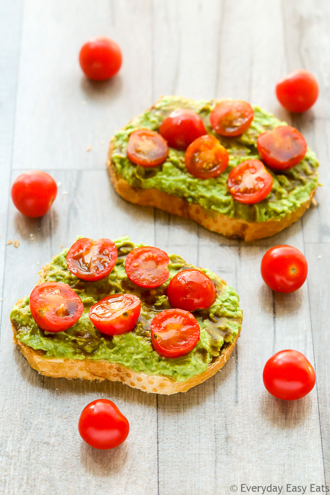 Overhead view of two slices of Tomato Avocado Toast with scattered cherry tomatoes on a wooden background.