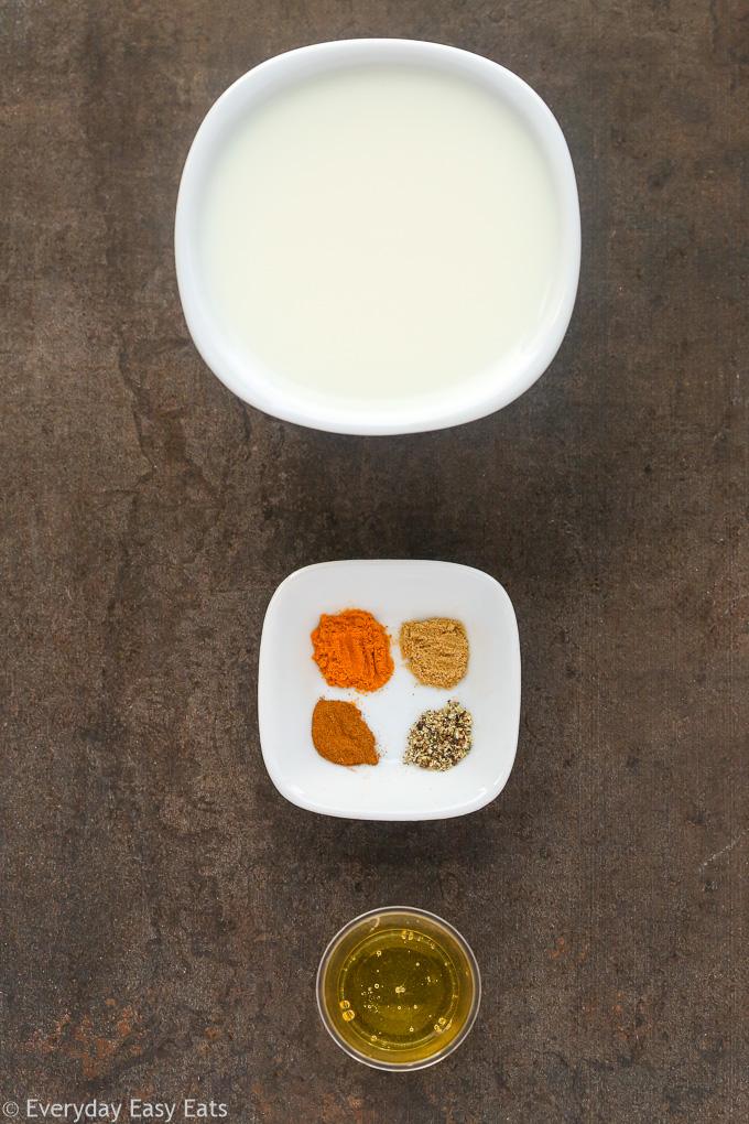 Overhead view of Golden Latte (Turmeric Milk) ingredients on a dark surface.