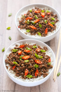 Overhead view of two bowls of Ground Beef Bulgogi with rice on a wooden surface with chopsticks on the side.