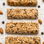 Overhead view of Chocolate Chip Granola Bars on a neutral background with scattered almonds and chocolate chips.