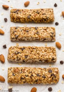 Overhead view of No-Bake Healthy Chocolate Chip Granola Bars on a neutral background with scattered almonds and chocolate chips.