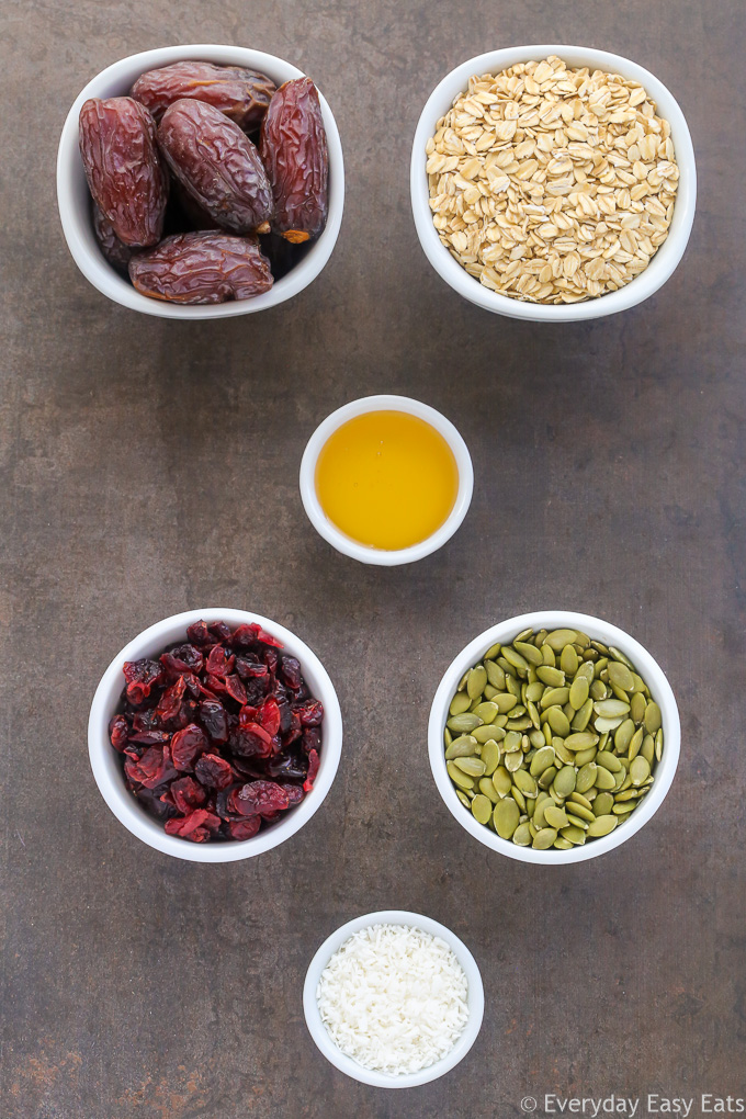 Overhead view of Healthy No-Bake Nut-Free Granola Bars ingredients in white bowls on a dark background.