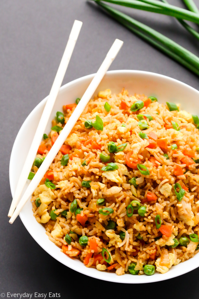 Budget-Friendly Meal: Overhead view of a plate of Chinese Fried Rice with chopsticks on a dark background.