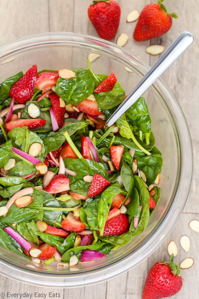 Strawberry Spinach Salad with Balsamic Dressing in a glass serving bowl on a wooden background