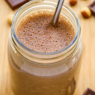 Overhead view of a glass of Peanut Butter Chocolate Protein Shake with straw on a wooden surface.