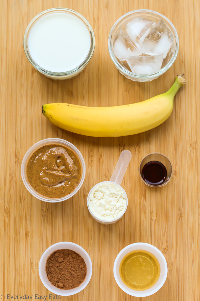 Overhead view of ingredients for Chocolate Peanut Butter Protein Shake on a wooden background.