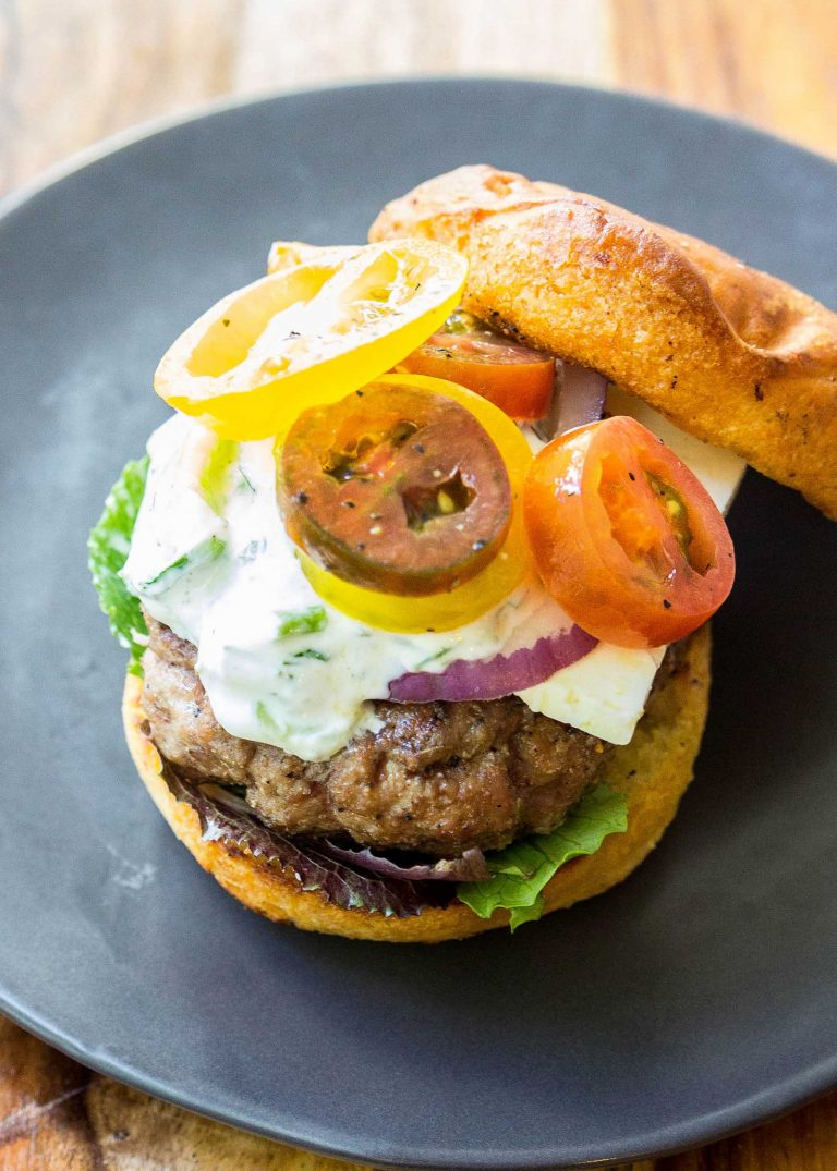 Healthy Grilled Meat Recipes for Summer: Overhead view of a Greek Lamb Burger on a blue plate.