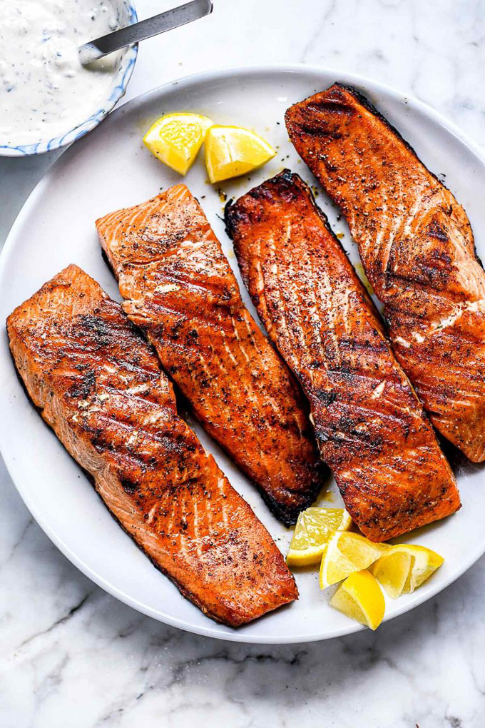 Healthy Grilled Meat Recipes for Summer: Overhead view of Grilled Salmon on a white plate.