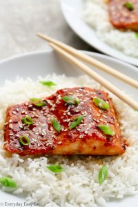 A plate of Baked Honey Sriracha Salmon sitting on a bed of white rice with chopsticks.