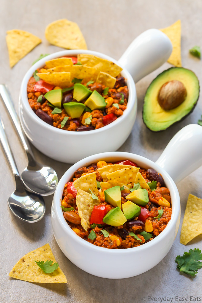 Overhead view of two bowls of Healthy Turkey Chili with spoons on the side on a beige background.