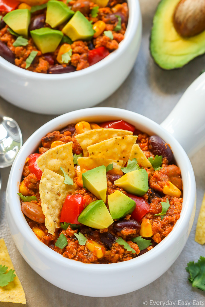 Close-up overhead view of a bowl of Healthy Turkey Chili on a beige background.
