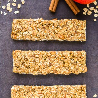 Overhead view of three Healthy Apple Cinnamon Granola Bars on a dark background.