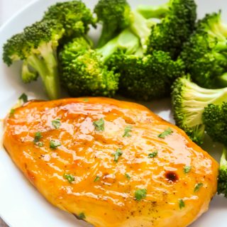 Close-up overhead view of Baked Honey Mustard Chicken Breasts in a white plate with steamed broccoli.