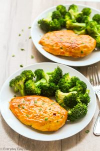 Overhead view of two plates of Baked Honey Mustard Chicken Breasts with steamed broccoli.
