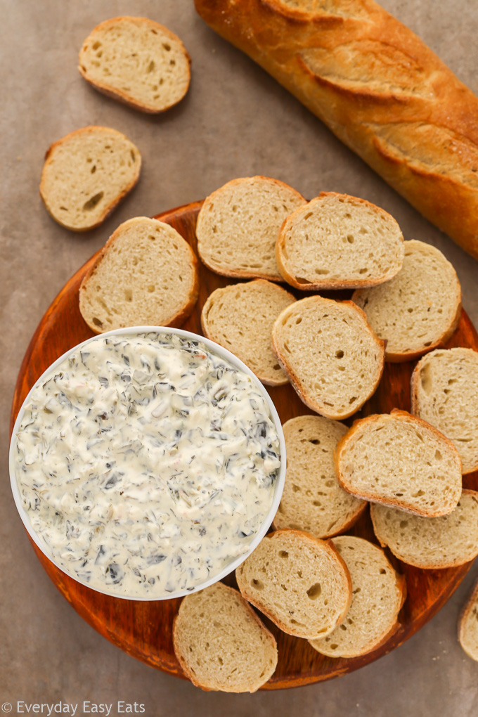 Close-up overhead view of a bowl of Keto Spinach Dip with baguette slices on the side.