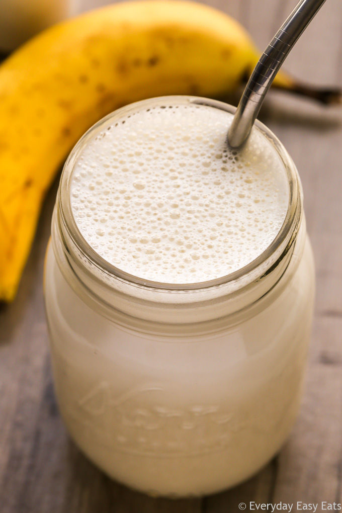 Close-up overhead view of Banana Protein Shake in a glass mason jar with a metal straw inserted on a wooden background.