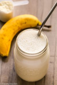 Overhead view of Banana Protein Shake in a glass mason jar with a metal straw inserted on a wooden background.