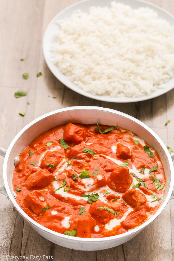 Overhead view of Easy Indian Butter Chicken in a silver serving bowl with a plate of white rice on a wooden background.