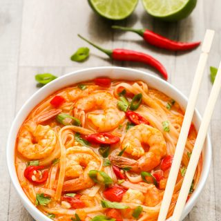 Side overhead view of Thai Shrimp Noodle Soup in a white bowl with chopsticks on a wooden background.