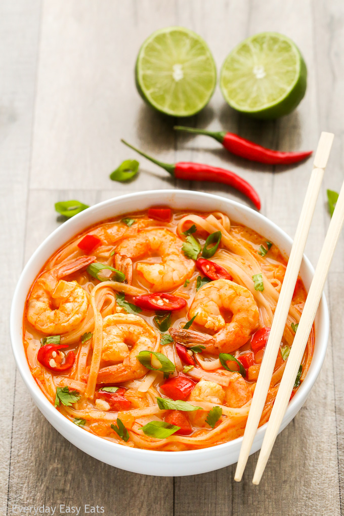 Side overhead view of Thai Spicy Shrimp Noodle Soup in a white bowl with chopsticks on a wooden background.