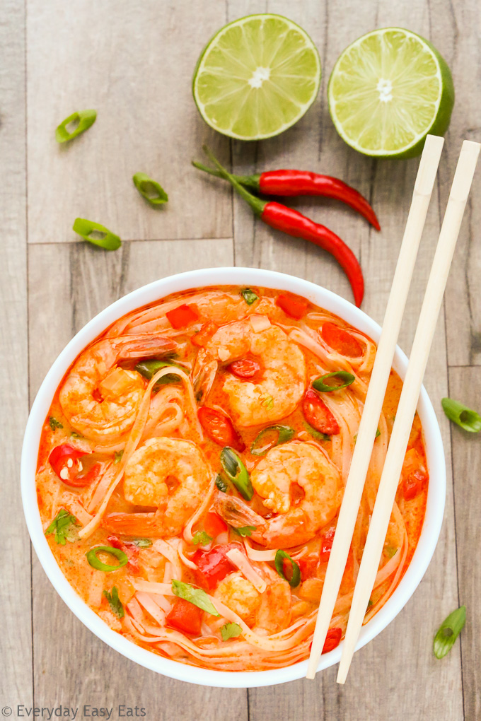 Overhead view of Thai Spicy Shrimp Noodle Soup in a white bowl with chopsticks on a wooden background.