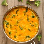 Overhead view of Broccoli Cheese Frittata in a skillet on a wooden background.