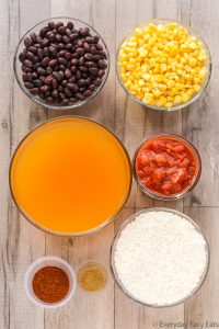 Overhead view of Vegetarian Burrito Bowl ingredients on a wooden background.