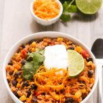 Overhead view of Vegetarian Burrito Bowl in a white bowl on a wooden background.