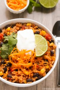 Close-up overhead view of Vegetarian Burrito Bowl in a white bowl on a wooden background.