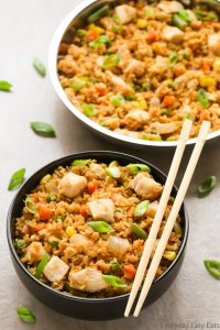 Overhead view of a bowl of Chicken Fried Rice with chopsticks on the side on a neutral background.