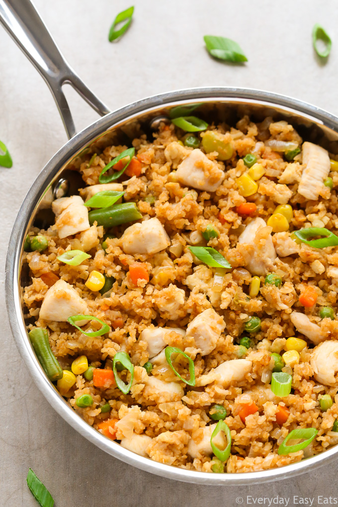 Close-up overhead view of a skillet of Chinese Chicken Fried Rice on a neutral background.