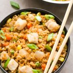 Close-up overhead view of a bowl of Healthy Chicken Fried Rice with chopsticks on the side on a neutral background.