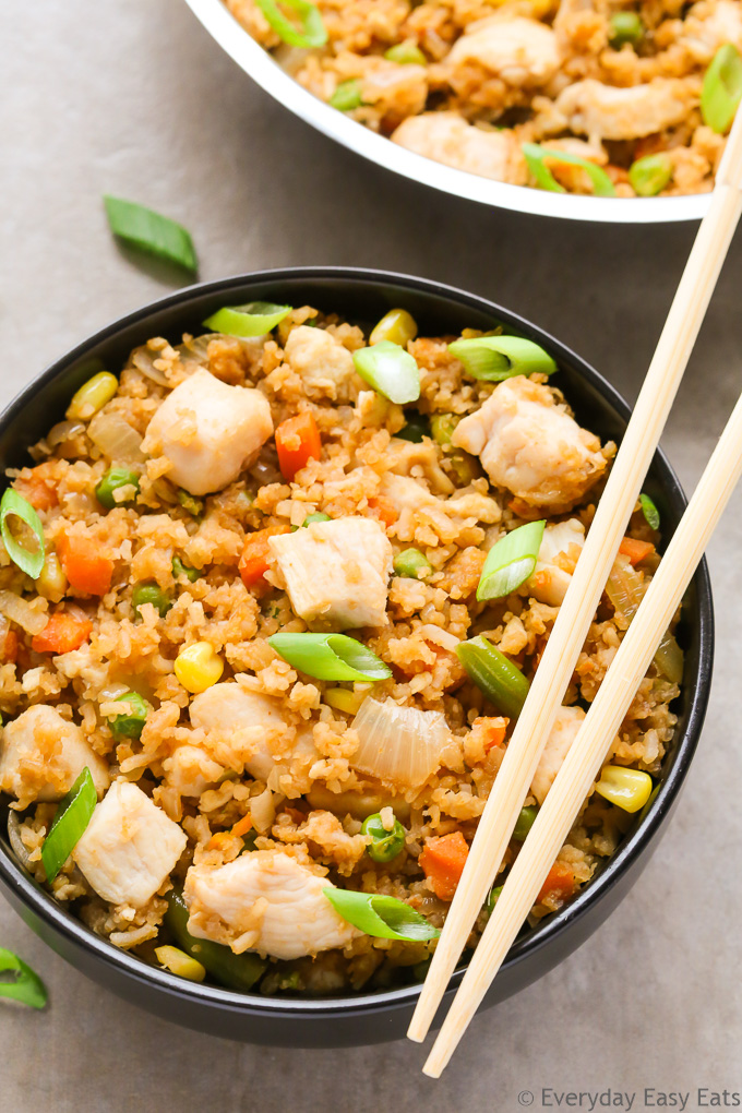 Close-up overhead view of a bowl of Chinese Chicken Fried Rice with chopsticks on the side on a neutral background.