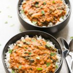 Overhead view of two bowls of Coconut Lentil Curry with spoons on the side on a neutral background.