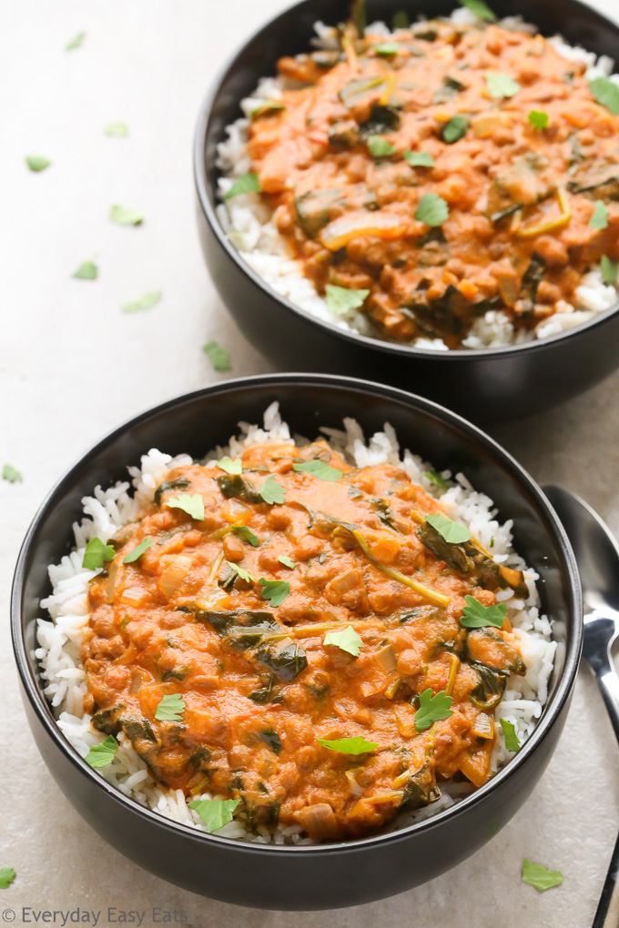 Close-up overhead view of two bowls of Coconut Lentil Curry with spoons on the side on a neutral background.