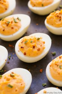 Close-up overhead view of spicy deviled eggs on a dark background.
