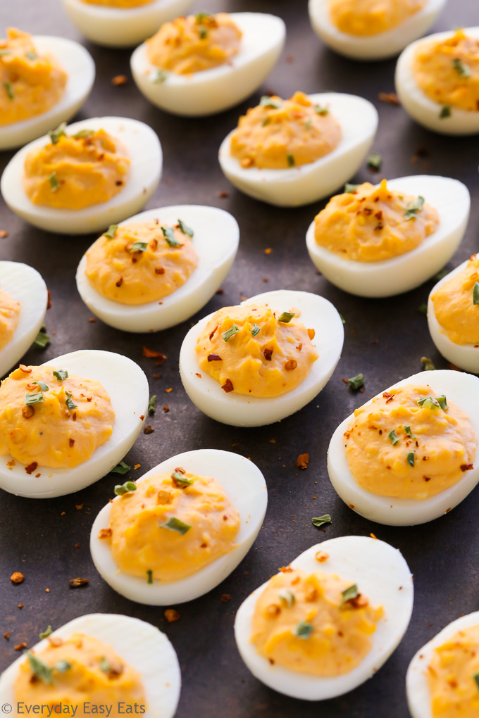 Overhead view of spicy deviled eggs on a dark background.